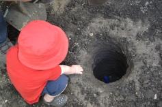 Nathan aide son papa en jetant les outils dans le trou des poteaux... très pratique !)