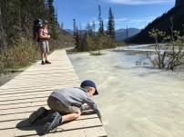 Nathan qui touche l'eau du lac depuis la passerelle